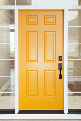 Sleek, yellow steel entry door with transom and double sidelites