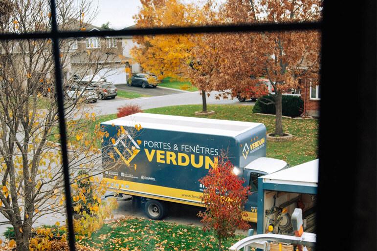 The view of a Verdun installation truck through a window from the interior of a home.