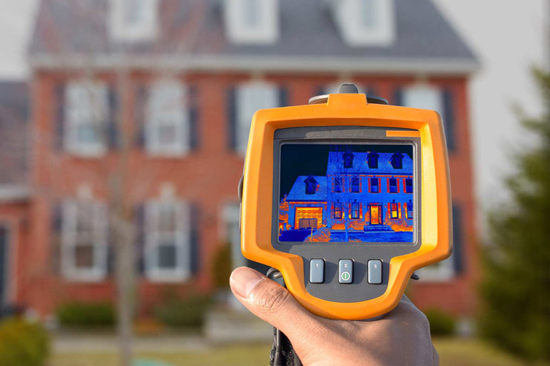 A heat loss tool is pointed at a house to determine energy efficiency of windows.