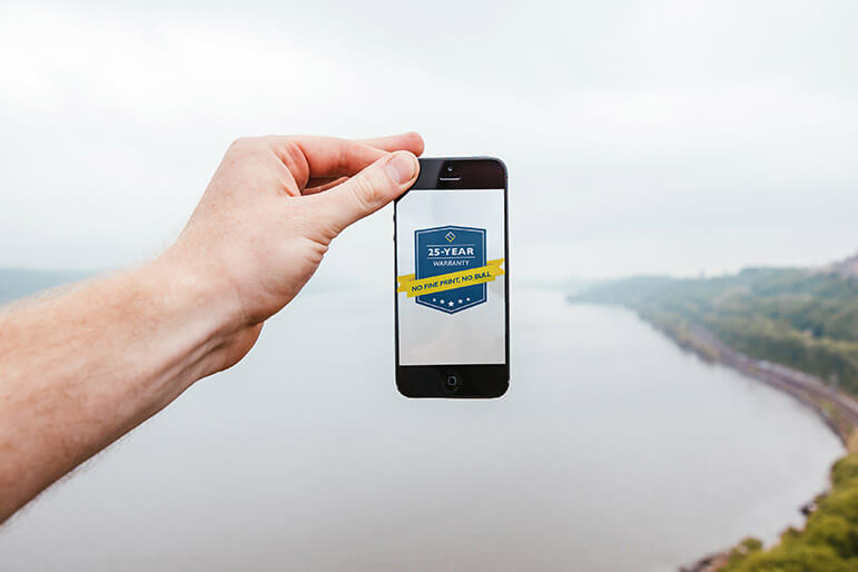 A phone is held over the horizon with an image of Verdun's new 25 year warranty.