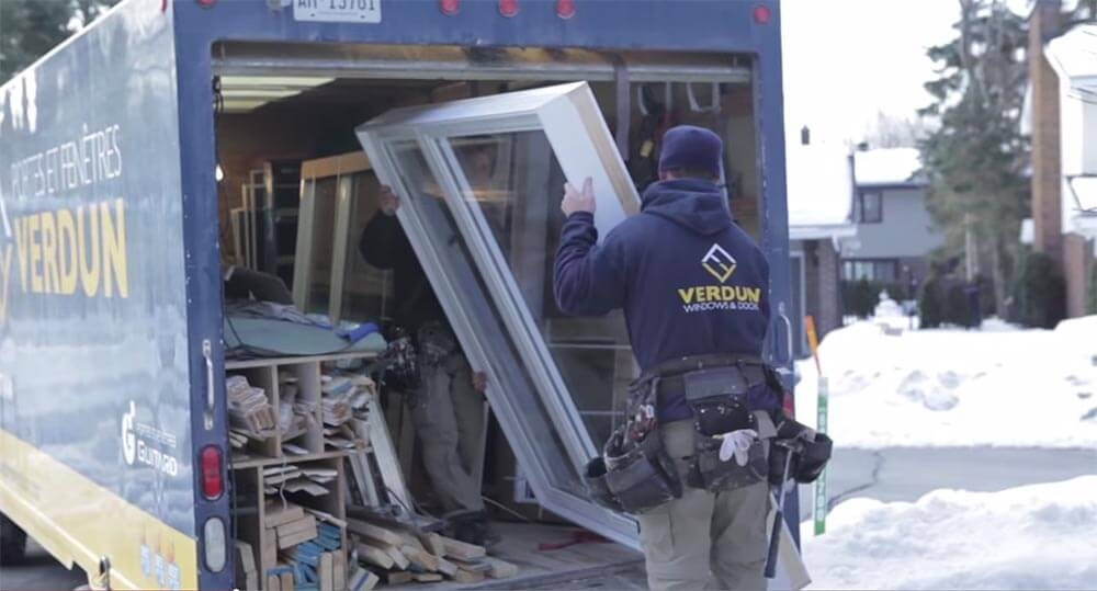 A Verdun window installer taking a replacement window out of the back of a truck in the winter time.