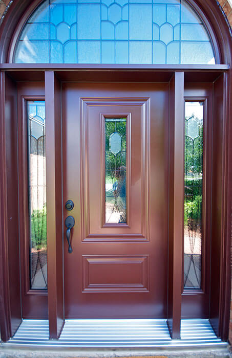 Gorgeous, chestnut steel entry door with half moon transom and double sidelites.
