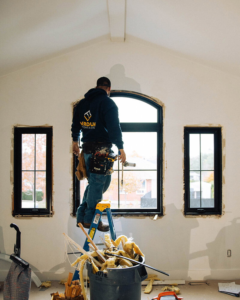 Verdun window installer puts a black casement window with top semi-circle transom in. The window has interior black paint.